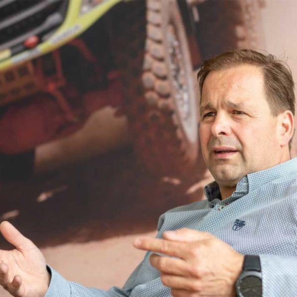 Close-up van Frank Tilburgs met zijn racetruck op de achtergrond.